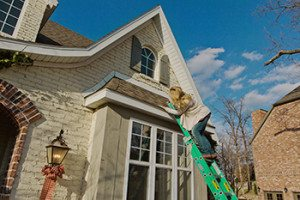 Client on ladder looking at roof