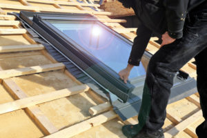 Roofing Contractor Uprgrading Roof And Adding Skylight